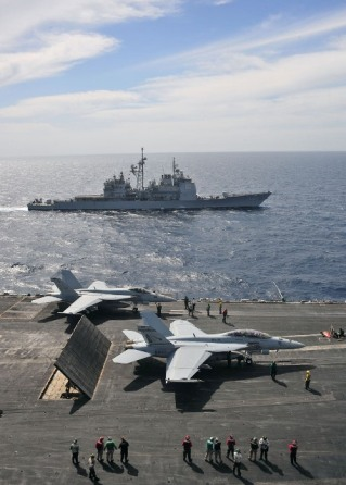 The Ticonderoga Class cruiser USS Leyte Gulf alongside the aircraft carrier USS Enterprise, while the latter conducts flight operations in the Red Sea. Enterprise stood by for potential action against the Gaddafi regime in Libya.  Photo: Jesse L. Gonzalez/US Navy.