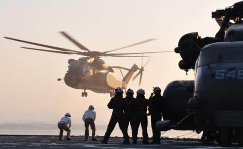 In the Sea of Japan, the day after the tsunami struck, MH-53 helicopters land aboard the amphibious dock landing ship USS Tortuga, which has been deployed to support earthquake and tsunami relief efforts in Japan. Photo: Lt. K. Madison Carter/US Navy.