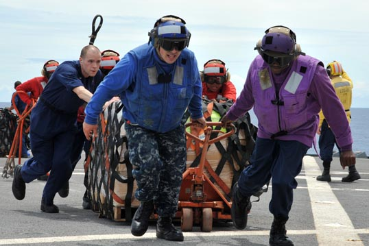 On their way from Singapore to Japan, sailors aboard the US 7th Fleet command ship USS Blue Ridge move pallets of humanitarian relief supplies across the ship's flight-deck during an underway replenishment with the USNS Rappahannock. Photo: Fidel C. Hart/US Navy.