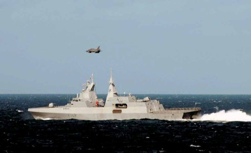 Pictured: The frigate Mendi kicks up a churning wake as a jet swoops low overhead. Photo: Clinton Wyness.